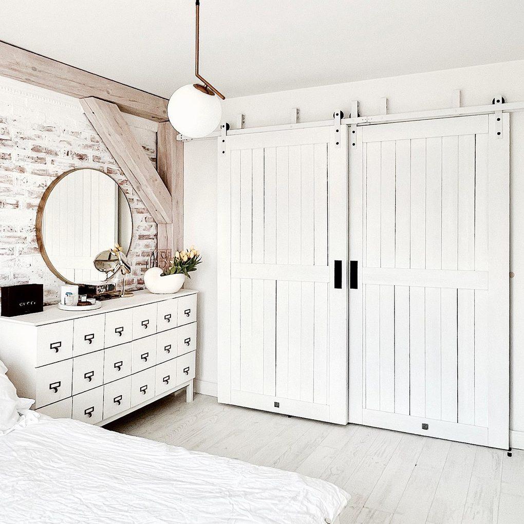 weißes schlafzimmer, doppelte weiße Schiebetür, weiße Kommode neben dem Bett im Schlafzimmer, Ziegel an der Wand in weiß gestrichen