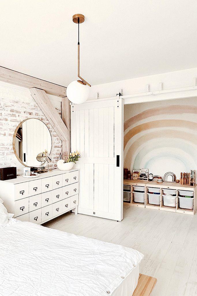 weißes schlafzimmer, Aussparung hinter Schiebetüren versteckt, weiße Kommode, weißes Holz im Schlafzimmer, Spielbereich in der Aussparung im Schlafzimmer, Ziegel an der Wand im Schlafzimmer, modernes rustikales Schlafzimmer