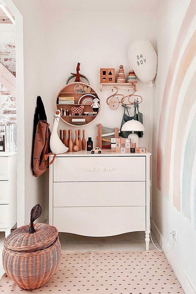 weißes schlafzimmer, Spielbereich im Elternschlafzimmer, hölzernes Kinderspielzeug, weiße Kommode im Kinderzimmer, Weidenkorb