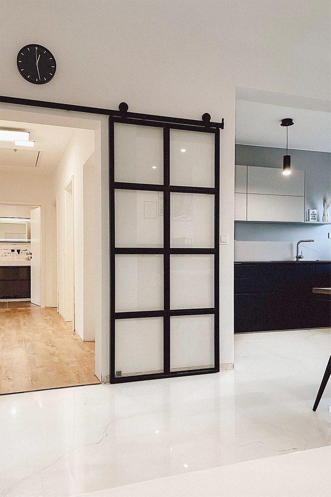 Glasschiebetüren, Metalltür mit transparentem Glas, schwarz-weiße offene Küche, schwarze Uhr an der weißen Wand