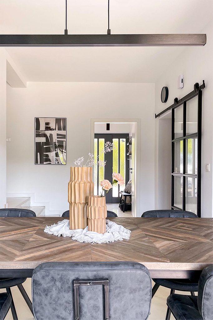dekorative Vasen, ein Tisch mit Fischgrätplatte, eine lange minimalistische Lampe über dem Esstisch, schwarze Accessoires in einem minimalistischen Interieur