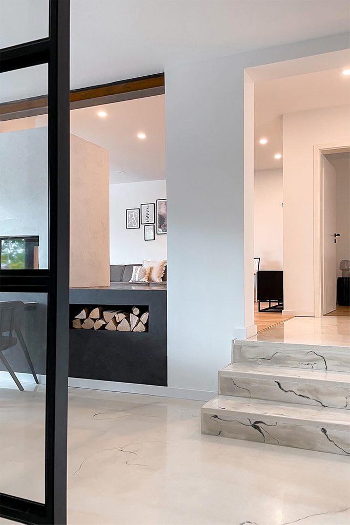 weiße Wände, heller Marmorboden, offener Wohnraum, schwarze Metallaccessoires in modernem Interieur