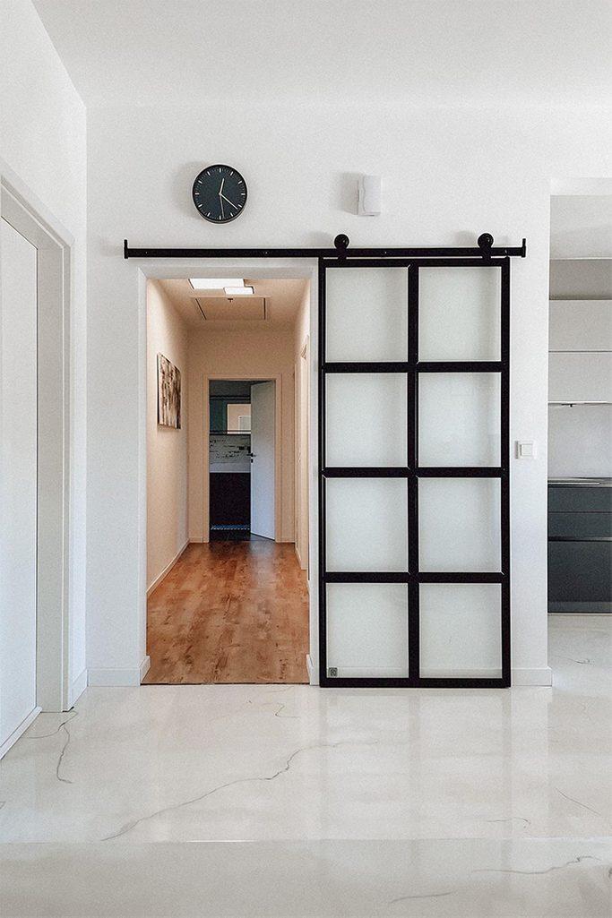Glasschiebetür, Glastür trennt den Flur, heller Marmorboden, weiße Wände und schwarze Accessoires, schwarze Uhr an weißer Wand, Metalltür mit Glas