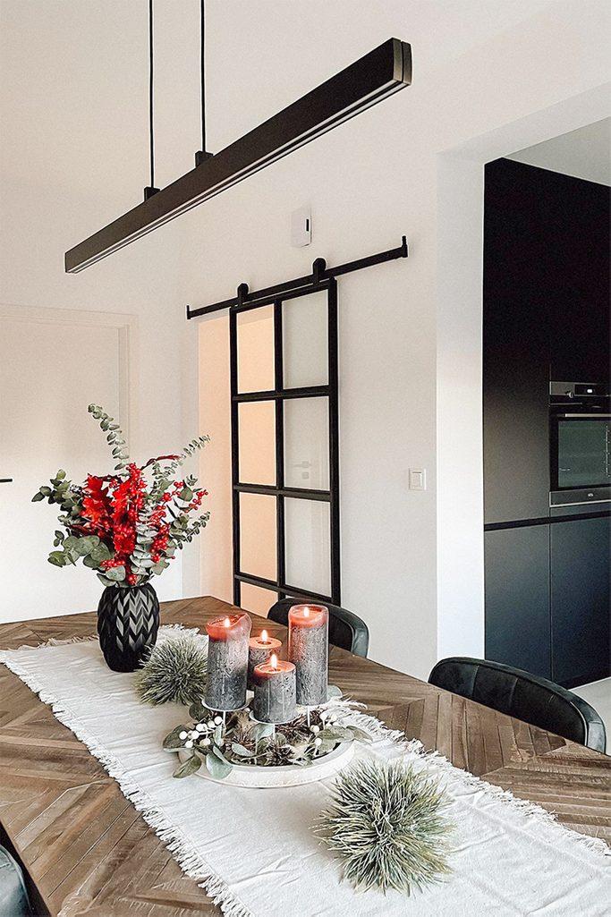 dekorative Kerzen auf dem Esstisch, dekorative Vase mit getrockneten Blumen auf dem Tisch, lange minimalistische Lampe über dem Tisch, Esstisch mit Fischgrätplatte, Glasschiebetür in einem Metallrahmen
