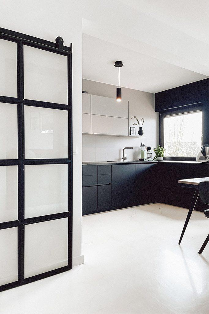 schwarz-weiße Küche, offene Küche mit Essbereich, minimalistische Küche mit schwarz-weißen Möbeln, heller Boden in der Küche, Glastür in einem Metallrahmen, minimalistische Pendelleuchte in der Küche
