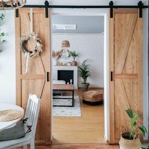 schmale Schiebetür, schmale Holztür am Schiebesystem, schmale Tür in der Küche, Schiebetür zwischen Küche und Wohnzimmer, Wohnung im Boho-Stil, Kranz an der Holztür, weiße Backsteinwand im Wohnzimmer